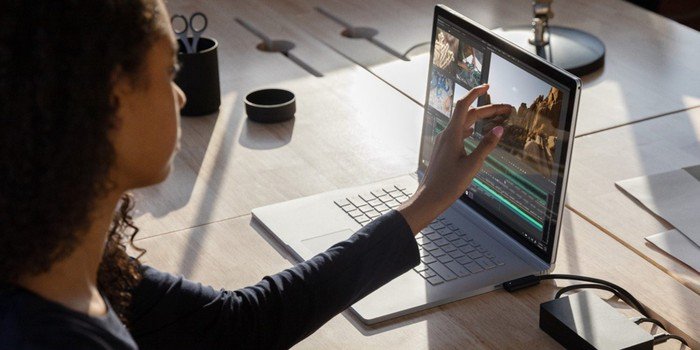Woman touching screen of laptop