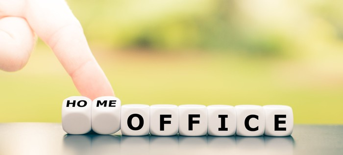 A person is flipping over some dice that spell the word home in front of the word office.
