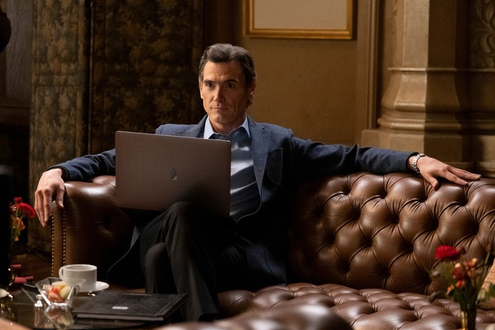Billy Crudup sitting on a couch with a MacBook