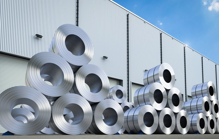Coils of aluminum sheet stacked outside a manufacturing warehouse.