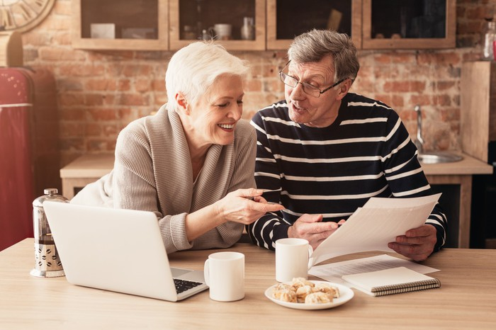 A retired couple are looking at documents with a laptop open on a table, smiling.
