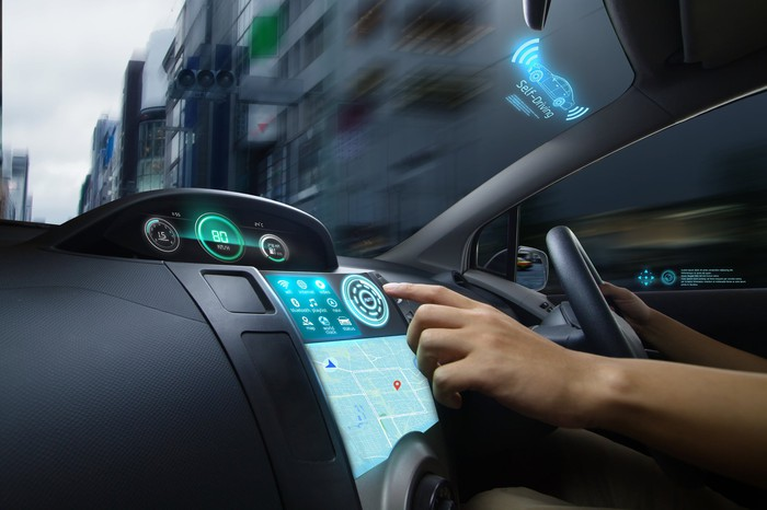 A hand reaches to touch a high-tech display on a car dashboard as it the other hand drives.