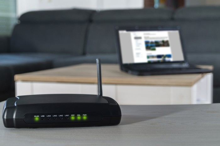 A mobile router sits on a table with a laptop behind it.
