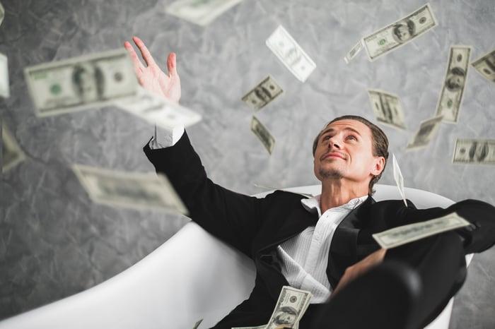 Man in a tuxedo sitting in a bathtub catching falling $100 bills.