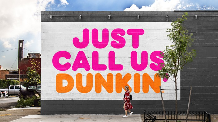 Large sign reading Just Call Us Dunkin painted on a wall, with woman walking past