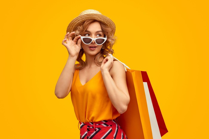 A fashionable woman in a hat and sunglasses with shopping bags slung over  her shoulder.
