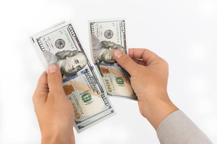 Hands holding $100 bills.