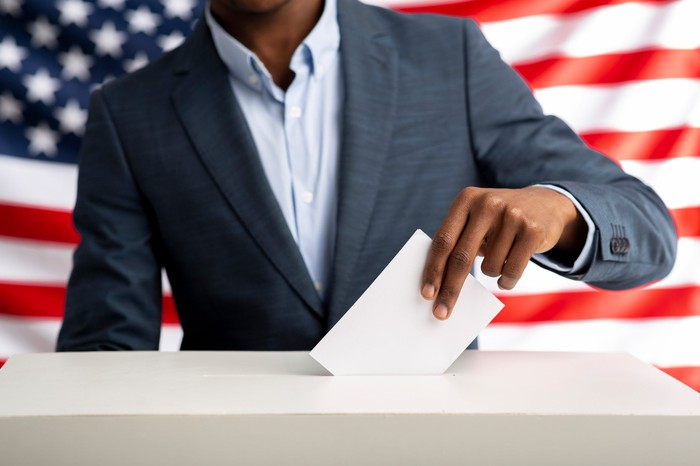 A person putting ballot in box with a U.S. flag in the background.