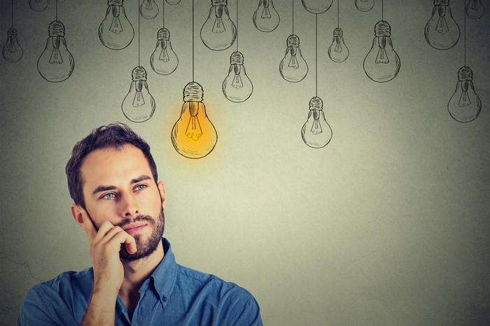 Man with hand on the side of his face with drawings of light bulbs in the background above him.