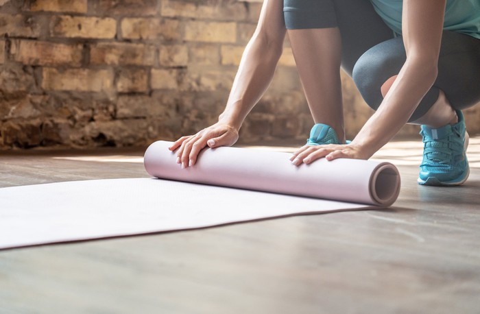 Woman rolling out a yoga mat.