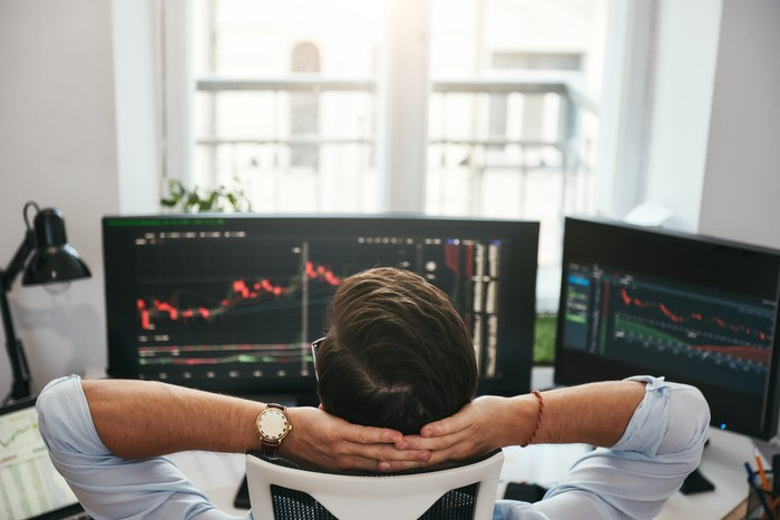 Man looking at stock charts on computers in office