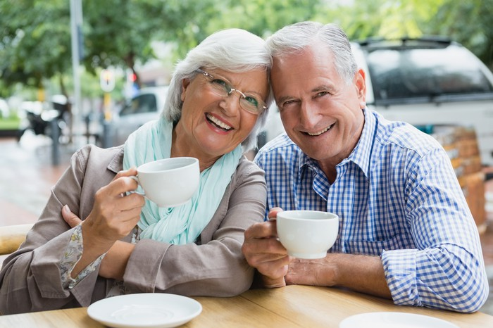 Smiling older man and woman holding mugs at a table outdoors