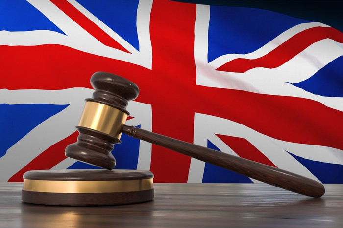 Gavel and block against a British flag in background