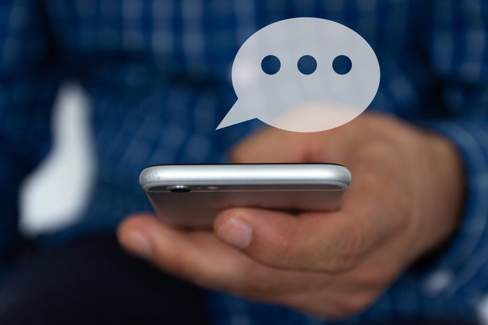 Hand of man typing text on mobile smartphone with chat icon appearing above phone.