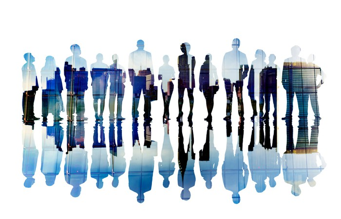 Silhouettes of businesspeople against a city backdrop.