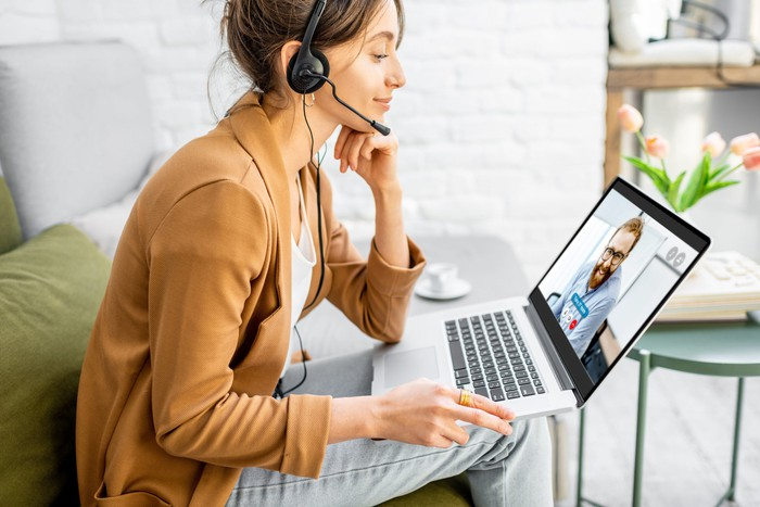 Woman working at home on a laptop while wearing a headset.