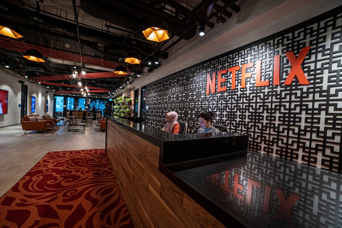 The reception desk at an office with the Netflix logo on the wall.
