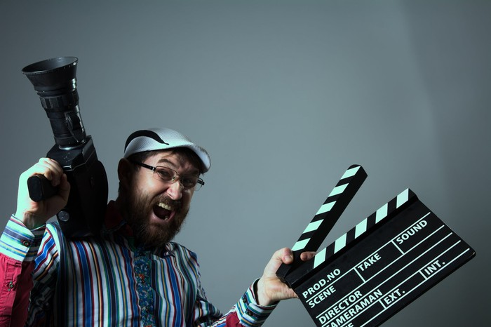 A beared man smiles at the camera, holding a movie camera in one hand and a clapper board in the other.