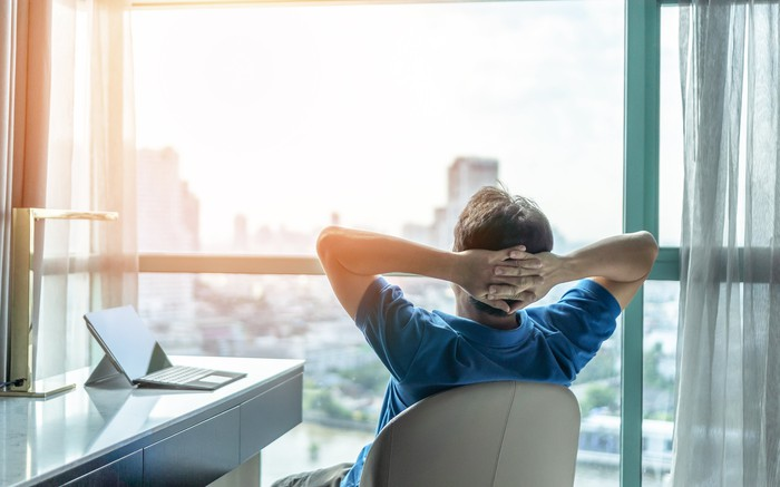A person leans back in a desk chair with their hands folded behind their head, staring out the window at a city skyline.