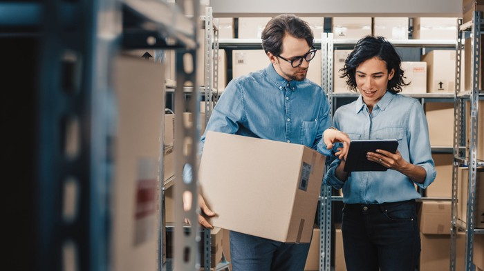 Man and woman staring at a digital tablet as they manage boxes inside a warehouse.