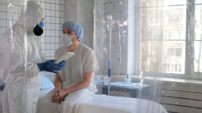Doctor in personal protective equipment talking to a patient in a mask