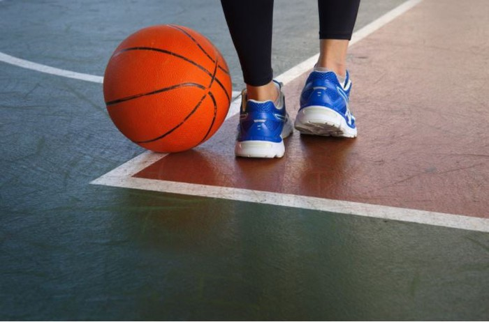 A basketball on the floor next to a player.