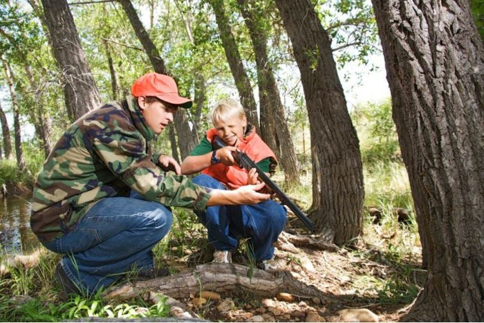 An adult teaches a youth to use a rifle as in hunting.