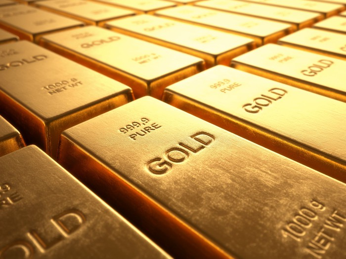 Several rows of gold bars stacked next to each other.