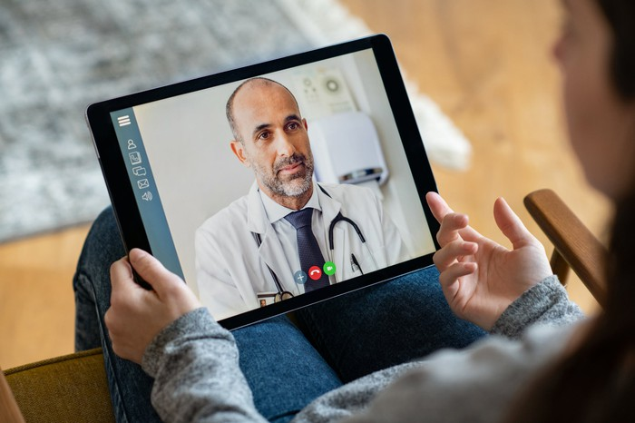 A person who uses a tablet to have a virtual appointment with a doctor.