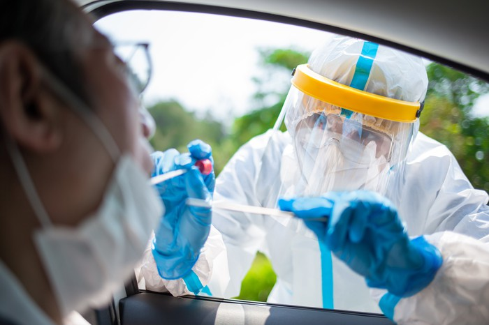 Medical worker testing for coronavirus at a drive-thru site.