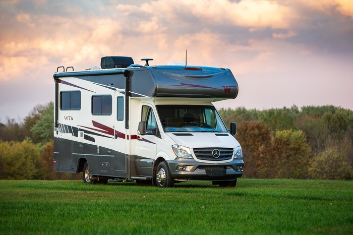 The Winnebago Vita model recreational vehicle sits out in a field under a cloudy sky.