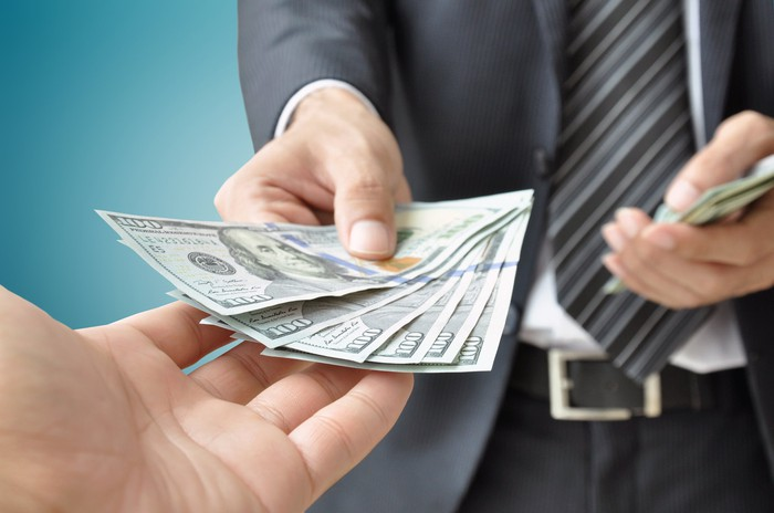 A person with an outstretched hand is being handed money by another person.