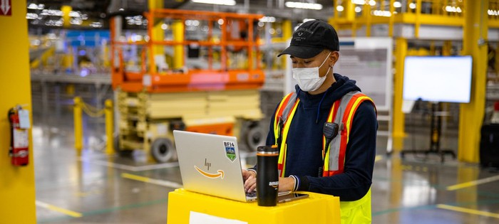 An Amazon warehouse worker wearing a mask