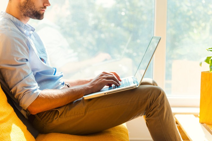Man sitting on couch, working on laptop at home