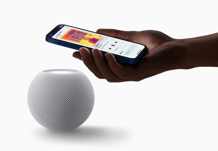 Hand holding an iPhone next to the HomePod Mini