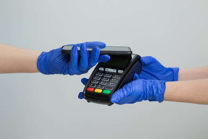 A person wearing protective glove paying with his phone while a person in gloves is holding a payment processing device.