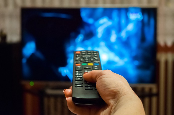 A hand holds a TV remote pointed at a big-screen television set in the background.