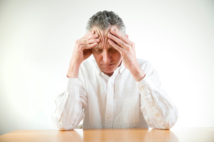 Older person at a table massaging their forehead.