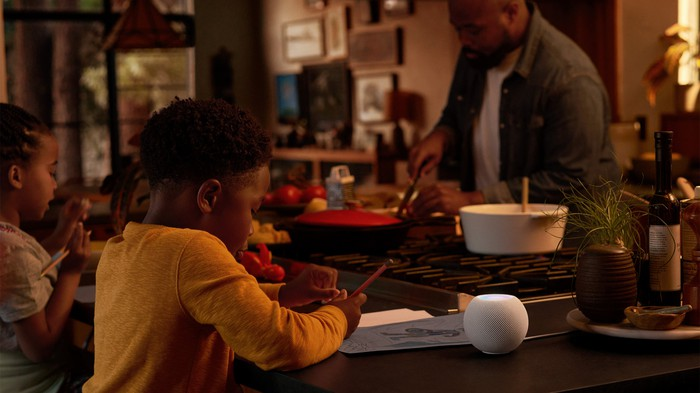 Two children sitting at a kitchen countertop with a man cooking on a stove across from them, with a HomePod Mini foregrounded on the counter
