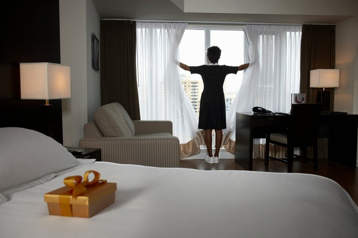 Person in hotel room looking out window, with box of chocolates on bed.