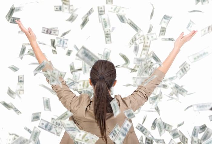 Woman throwing dollar bills in the air.