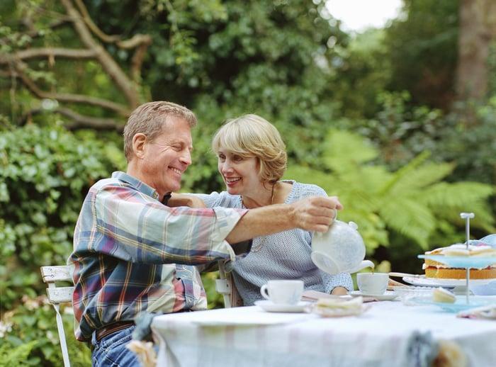 Mature looking couple drinking tea in a garden.