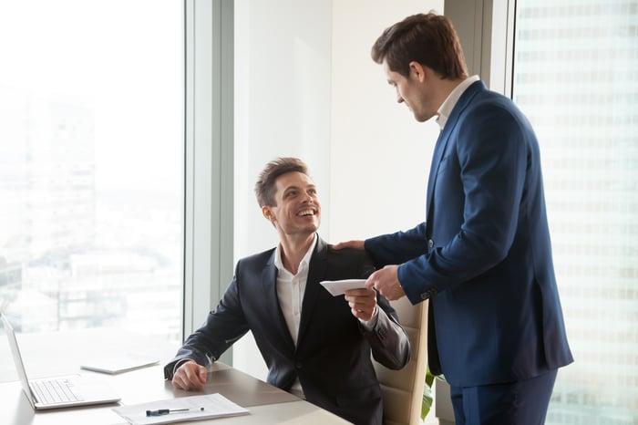 Boss handing employee an envelope