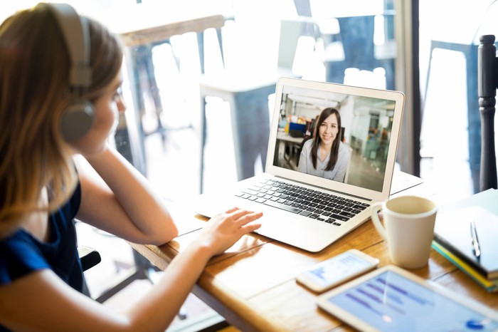 Woman wearing headphones and participating in a video conference call on a laptop in a cafe.