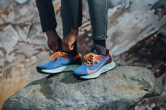 Close-up of person leaning down and adjusting their Nike sneakers while standing on a rock