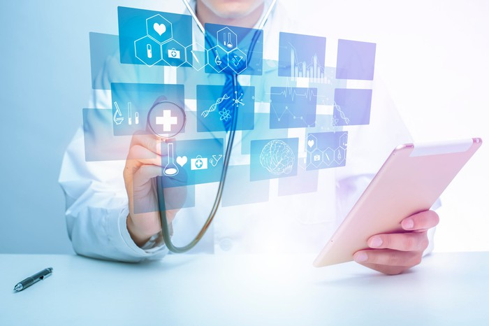 Doctor with a tablet in hand, with medical icons superimposed.