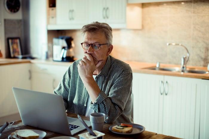 Older man sitting behind a laptop looking worried