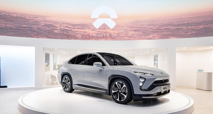 A silver NIO EC6, a sporty upscale electric crossover SUV, on an auto-show display stand.
