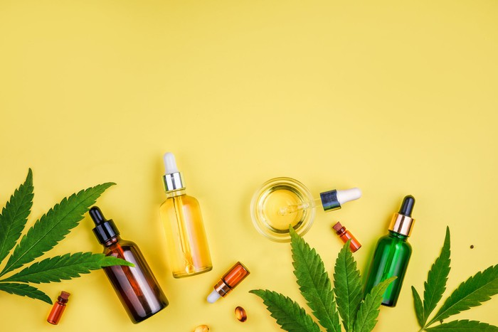 Several glass bottles with cannabis tinctures are scattered on top of a few cannabis leaves.