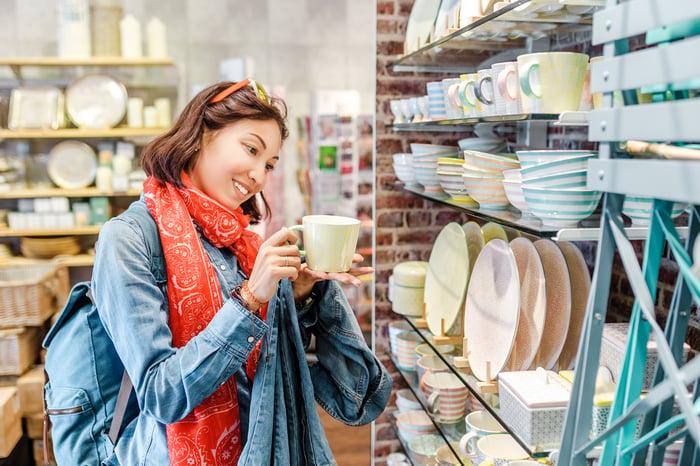 Woman examining a coffee mug in a housewares store